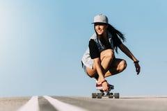 Montar a caballo hermoso de la mujer del patinador en su longboard Imágenes de archivo libres de regalías