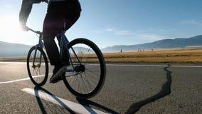 Montar a caballo hermoso joven del hombre en la bicicleta del vintage en la carretera nacional Individuo deportivo que completa u metrajes