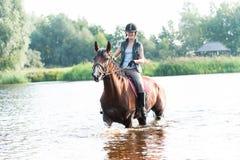 Montar a caballo joven alegre del adolescente a caballo en el río en la mañana Fotos de archivo