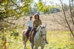 Montar a caballo joven de los pares Imagen de archivo