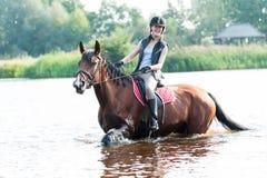 Montar a caballo joven del adolescente de Smililng a caballo en el río Imagenes de archivo