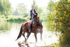 Montar a caballo joven del adolescente a caballo en el río en la madrugada Imagen de archivo