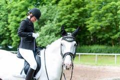 Montar a caballo joven del adolescente que la prepara a caballo ropa a COM Fotos de archivo libres de regalías