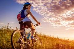 Montar a caballo joven del ciclista en campo del verano Concepto sano de la forma de vida Fotos de archivo libres de regalías