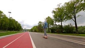 Montar a caballo joven del patinador en Longboard almacen de video