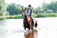 Montar a caballo joven sonriente del adolescente a caballo en el río Fotografía de archivo libre de regalías