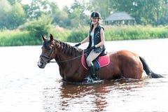 Montar a caballo joven sonriente del adolescente a caballo en el río en el MES temprano Fotos de archivo libres de regalías