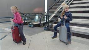 Montar a caballo juguetón del adolescente de las muchachas en la maleta en aeropuerto en fondo de la escalera móvil metrajes