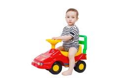 Montar a caballo lindo del niño en un coche de bebé Imagen de archivo libre de regalías