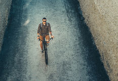 Montar a caballo masculino joven en la bici abajo de la calle, visión superior del ciclista Concepto de reclinación urbano de la  Imagen de archivo libre de regalías