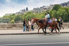 Montar a caballo montado de la policía más allá de los espectadores en el puente en París Fotografía de archivo