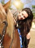 Montar a caballo moreno bonito joven y caricia de su caballo al aire libre fotos de archivo