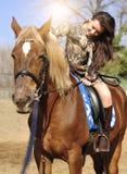Montar a caballo moreno bonito joven y caricia de su caballo al aire libre imagen de archivo libre de regalías