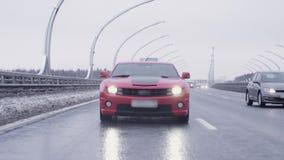 Montar a caballo rojo del coche del músculo hacia cámara en la carretera almacen de metraje de vídeo