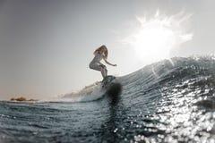 Montar a caballo rubio de la muchacha en el wakeboard en las rodillas de doblez imagen de archivo libre de regalías