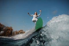 Montar a caballo rubio de la muchacha en el wakeboard verde en las rodillas de doblez fotografía de archivo