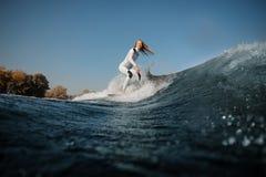 Montar a caballo rubio sonriente de la muchacha en el wakeboard en las rodillas de doblez imagenes de archivo