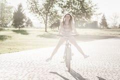 Montar a caballo sonriente de la muchacha en la bicicleta Foto de archivo