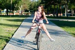 Montar a caballo sonriente de la muchacha en la bicicleta Fotografía de archivo