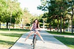 Montar a caballo sonriente de la muchacha en la bicicleta Imágenes de archivo libres de regalías