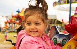 Montar a caballo sonriente lindo feliz de la niña en el carrusel en día de verano Foto de archivo libre de regalías