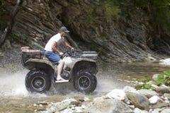 Montar un ATV a lo largo de la cama de un río de la montaña foto de archivo