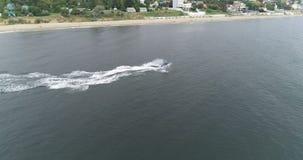 Montar un esquí del jet a lo largo de la costa almacen de video