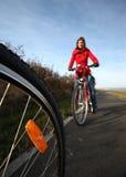 Montar una bicicleta en un parque en un día encantador Imagen de archivo
