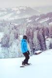 Montar una snowboard abajo de la cuesta Foto de archivo