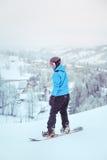 Montar una snowboard abajo de la cuesta Fotos de archivo