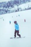 Montar una snowboard abajo de la cuesta Imágenes de archivo libres de regalías