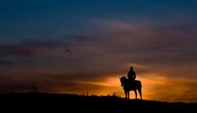 Montare un cavallo nel tramonto Immagini Stock Libere da Diritti