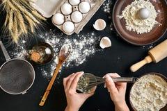 Montatura delle uova Il primo piano delle mani del cuoco unico sbatte le uova su un fondo nero Vista da sopra fotografia stock libera da diritti