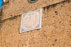 MONTBRIO台尔CAMP,西班牙- 2016年6月6日:在墙壁上的老太阳时钟在Montbrio del Camp,塔拉贡纳, Catalunya,西班牙 库存图片