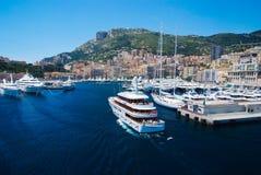 Monte Carlo, Monaco - 8 décembre 2009 : le bateau entrent dans le port de mer avec des maisons sur le paysage de montagne Club et Image stock