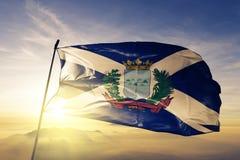 Monte Cristi Province of Dominican Republic flag textile cloth fabric waving on the top sunrise mist fog. Beautiful stock photo