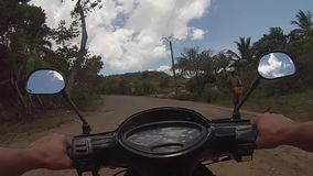 Monte d'une motocyclette de scooter sur les routes malgaches banque de vidéos