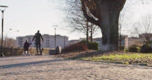 Monte de fille d'enfant de fille segway avec son papa dans la ville Future technologie moderne de transport Famille actif Trottoi banque de vidéos