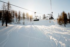 Monte de l'ascenseur de chaise par la forêt du haut alpin Photographie stock
