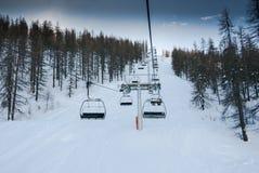 Monte de l'ascenseur de chaise par la forêt images stock