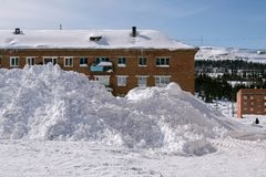Monte de neve perto do prédio na vila imagem de stock
