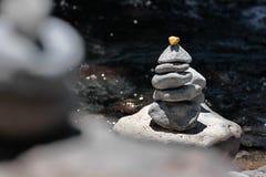 Monte de pedras com a pedra dourada pelo córrego Fotografia de Stock