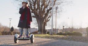 Monte de port de sourire heureuse de portrait de casque de sécurité de fille d'enfant de fille segway au parc de ville Enfance, a banque de vidéos
