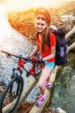 Monte en bicicleta adolescente con las bicis de las señoras en parque del verano Bici para mujer del camino para correr Imagenes de archivo