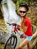 Monte en bicicleta adolescente con las bicis de las señoras en parque del verano Bici para mujer del camino para correr Fotografía de archivo libre de regalías