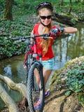 Monte en bicicleta adolescente con las bicis de las señoras en parque del verano Bici para mujer del camino para correr Foto de archivo libre de regalías
