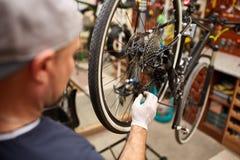 Monte en bicicleta al mecánico en un taller en el proceso de la reparación Imagen de archivo libre de regalías