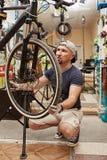 Monte en bicicleta al mecánico en un taller en el proceso de la reparación Foto de archivo
