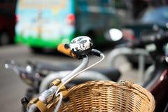 Monte en bicicleta con la cesta de mimbre y el coche en el fondo Imágenes de archivo libres de regalías
