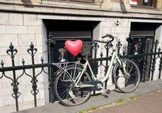Monte en bicicleta con un corazón en el tronco en Amsterdam Fotos de archivo libres de regalías